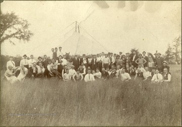 "The group of approximately 60 men, wearing bowler, panama and fedora hats, posing with an Irish harp, fiddles, cooking pots and an 8 foot stove-pipe. It was believed to be taken at the Green Sulphur Annual Fair. The man at the extreme right is Timothy Field but all others are unidentified. Other information inscribed on the back includes: ""Suspension construction walled circular tent, 2 poles & 4 guide wires, see tent peg at extreme left, Privy at extreme right ..."". The photograph was purchased by Stephen Trail in Hinton, West Virginia."