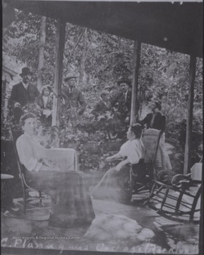 Unidentified men and women socialize on porch of the Flanagan Cabin in Summers County.
