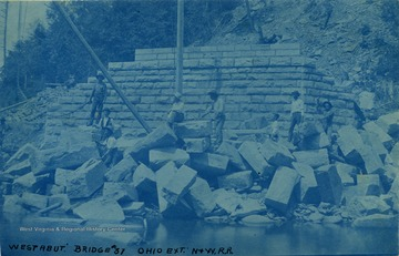 Unidentified workers stand among cut stones used in the construction of bridge abutments (such as one in the background). The poles in the photograph are part of the pulley used to place the stones.