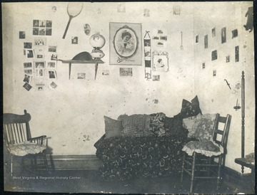 Dorm room walls decorated with photograph, posters and a tennis racket.