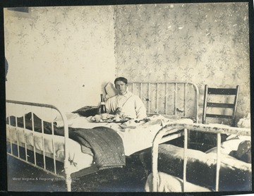 WVU student Leonard Hall enjoying a meal in bed, in his dorm room.