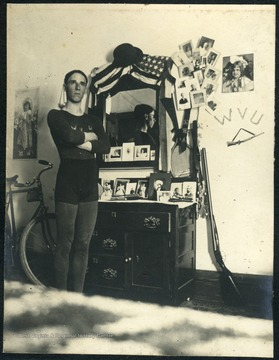 Unidentified student dressed in athletic attire of jersey, shorts and tights, poses a dorm room in Episcopal Hall. Note a bike on one side of the dresser and a gun on the other side.