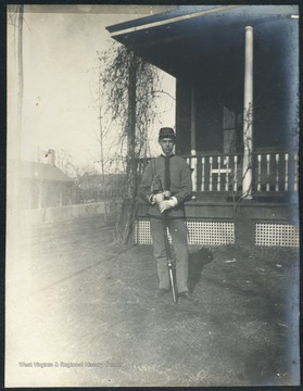 Unidentified student wearing cadet uniform stands holding his weapon.