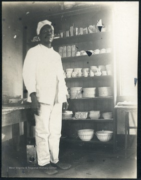 Unidentified African-American man wearing white, stands in a pantry area of the dormitory.