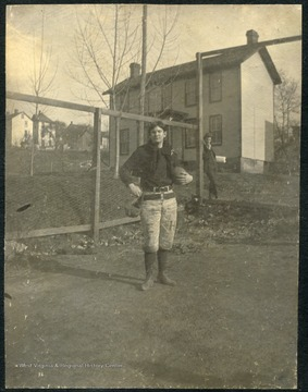 "WVU student poses with a football, wearing a uniform with ""E"" & ""H"" stamped on his pants, for ""Episcopal Hall""."