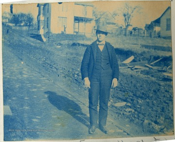 Unidentified young man stands on a brick paved road.
