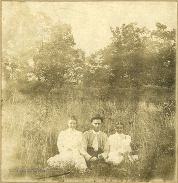 Sitting in the tall grass, Ada Enid Haldeman, Arthur C. Thomas and Olivia L. Haldeman.