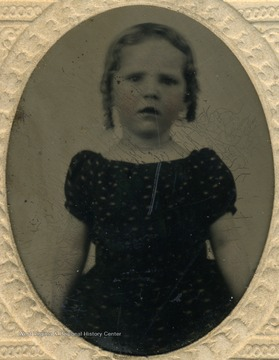 A young girl wearing rounded neckline and puffy, short sleeved dress, popular fashion for children in the mid 19th century.