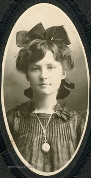 Unidentified girl adorned with hair ribbon and locket.