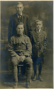 Group portrait of three members of the Birchinal family. One is wearing an army uniform and the elderly man and young boy are standing.