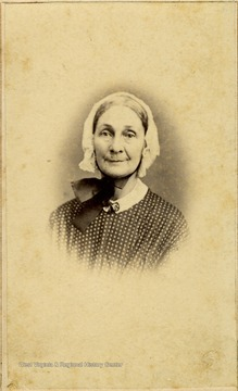 An older woman in a bonnet and polka dot dress. There is a revenue stamp on the back of the photograph indicating a tax was paid to support the Federal War effort during the Civil war.