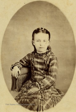Young girl in a plaid dress. She is unidentified.