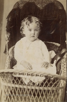 Toddler in a lace dress. Could be a boy or girl since very young boys wore dresses also.
