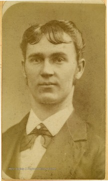 Young man with styled hair wearing a suit and bow tie.