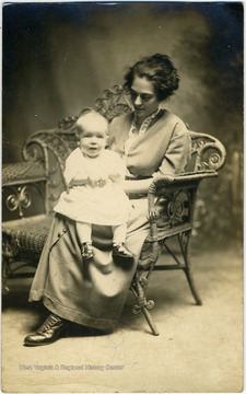 Postcard photograph of an unidentified woman holding an infant in her lap.
