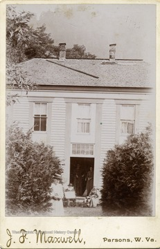Rufus Maxwell and his wife Sarah Bonnefield Maxwell sit outside by the front open door, others are not identified. Photo taken at the old Maxwell home.