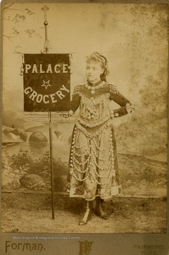 "Young girl wearing a costume and holding a banner embossed with words, ""Palace Grocery""."