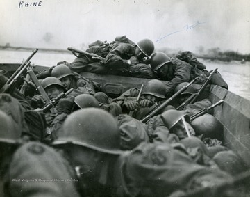 "Information included with the photograph, ""Troops of the Third U.S. Army crouch low as enemy fire opens during their crossings of the Rhine in assault boats at Oberwesel, Germany. The Army first forged the river March 22, 1945."" Note the label ""me"" on the photograph most likely points to Raymond Young, infantryman and combat photographer."