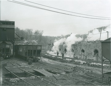 Loaded Baltimore & Ohio Rail Cars stand across from the unidentified workers and the ovens operated by Elkins Coal and Coke Company.