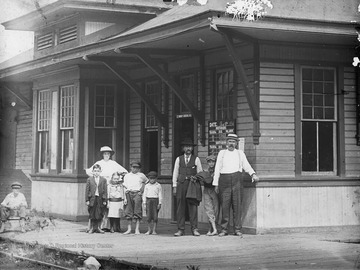 Group of people stand outside of railroad depot. Departure times for several trains on the wall behind men on the right.