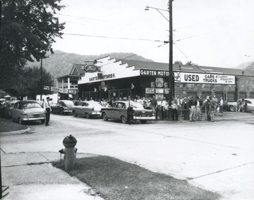 A crowd gathers around the new Ford automobiles parked in front of the store lot.