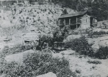 Two horses stand outside of the farm house located in the rocky terrain.