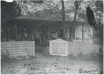 People sit on the porch of the fenced off building. No subjects identified.