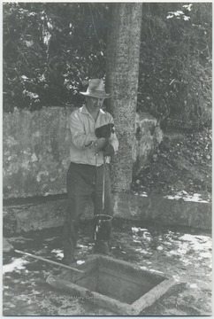 Unidentified man pulls up water from a well.