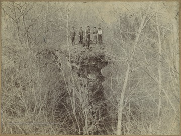 Five unidentified man stand by the edge of the cliff.
