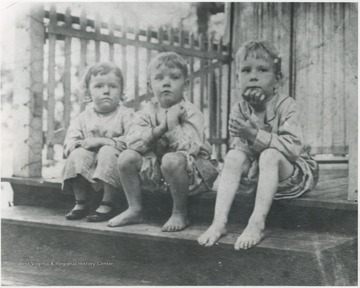 (From left to right) Dorothy Daly, Robert Turner, and Andy Timberlake sit on the porch steps.