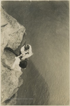 Two unidentified subjects climb along the rocks that tower above the river.