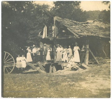 A group of unidentified subjects pose infront of the old mill.