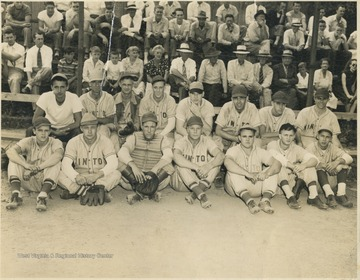 Unidentified players sit together in front of the on-looking crowd.