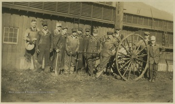 Group of men pose by the hose wheel. Subjects unidentified.