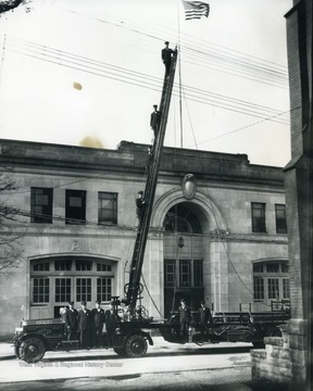 Print number 1266. Firemen pose on the ladder and the truck.  Doc, the Morgantown Fire Department dog, is on the truck beneath the ladder.