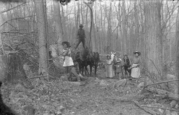 The two women pictured are holding tools, one an axe, preparing for some type of clearing work. Location is mostly likely in or near Preston County.