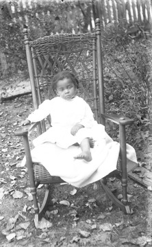 Young child wearing a crisp, white dress poses in large rocker.