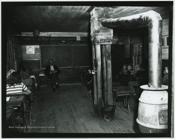 A teacher and his students of various ages, are pictured in a classroom. Subjects unidentified.
