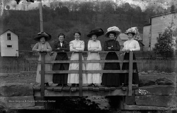 Unidentified group of women, some wearing fashionable hats of the day, lean on the bridge railing.