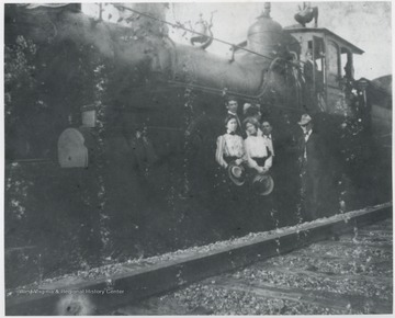 Tall man pictured next to the train is R.O. Murrell. Other subjects unidentified.