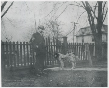Murrell pictured in his yard with a dog. The house is located on the corner of 5th Avenue and Summers Street. C&O Commissary is pictured in the background.