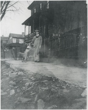 Murrell pictured outside the fence that surrounds his house with his dog. The home is located on the corner of 5th Avenue and Summers Street.