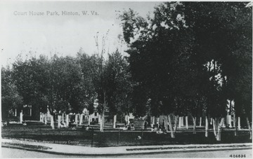 Street view of the park. A group of people are scattered across the lawn.