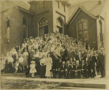 Located on the corner of 3rd Avenue and Ballengee Street, a group of church members pose in front of the building and on the steps. The reverend at the time the picture was taken was Rev. Gates. Subjects unidentified.