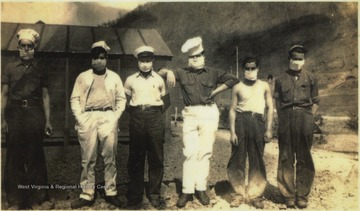 Six unidentified men wearing quarantine masks due to a death from spinal meningitis. The quarantine lasted 30 days for all personnel at the Civilians Conservation Corps (CCC) camp. The CCC constructed projects including bridges, buildings, overnight cabins, retaining walls, roads, dams, towers, picnic areas, and drainage systems.