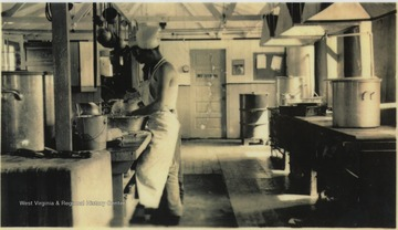 Two unidentified men working in the kitchen. The camp required two cooks per shift of 24 hours followed by 24 hours off.