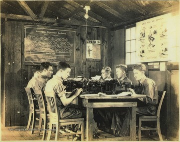 Six young men sit behind typewriters. The class cost 50 cents a month to participate in. Subjects unidentified.