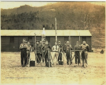 A group of young men stand behind surveying equipment. Subjects unidentified.