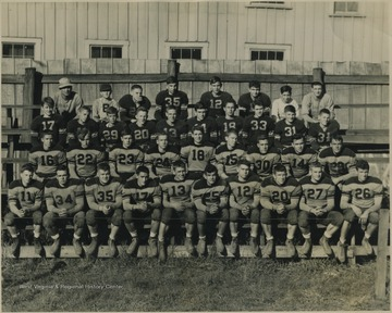 Football players sit on the bleachers for their team portrait. Subjects unidentified.