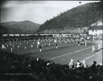 The band plays on the field while spectators watch from the bleachers. Referees pictured in conversation on the bottom right.